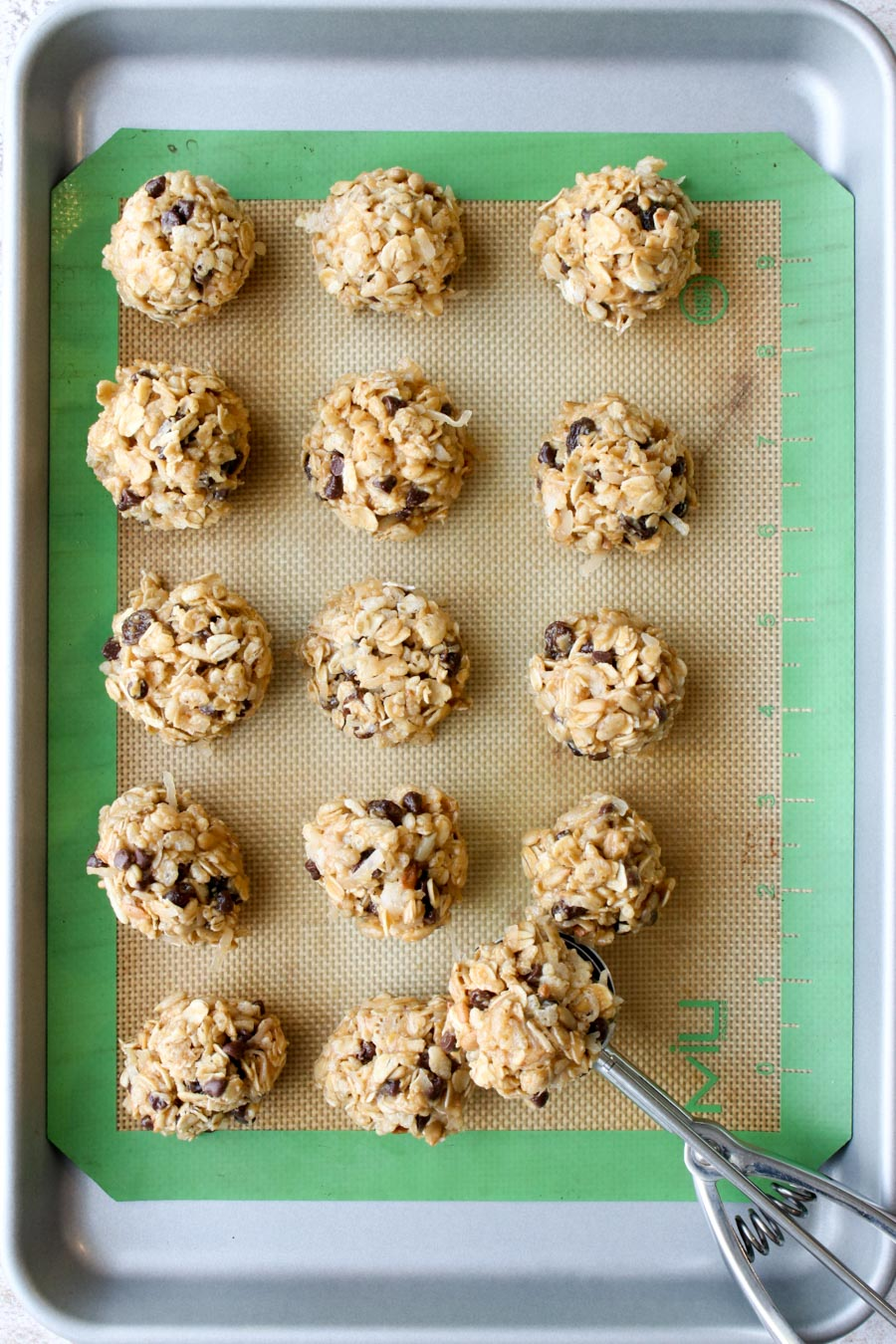 Peanut Butter Energy Balls on a cookie sheet with a scoop.