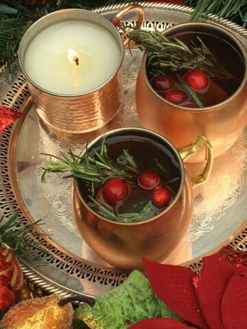 A fancy silver tray with a burning candle and two gold mugs of cocktail garnished with rosemary and cranberries