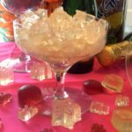 Champagne glass on a pink cloth filled with gummy candy