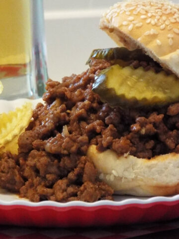 sloppy joe with pickle spilling out of a bun