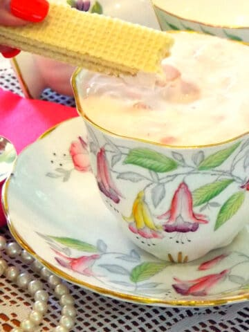 A tea cup with filled with pink pudding with cookie being dipped into it.