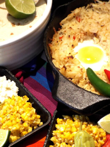 a pan of has browns topped with eggs with corn, lime, tortillas, on side
