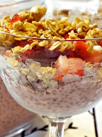 A fancy dish filled with yogurt topped with granola and strawberries