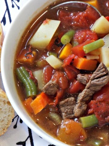 A bowl of beef soup with potatoes, beans, carrots, tomatoes