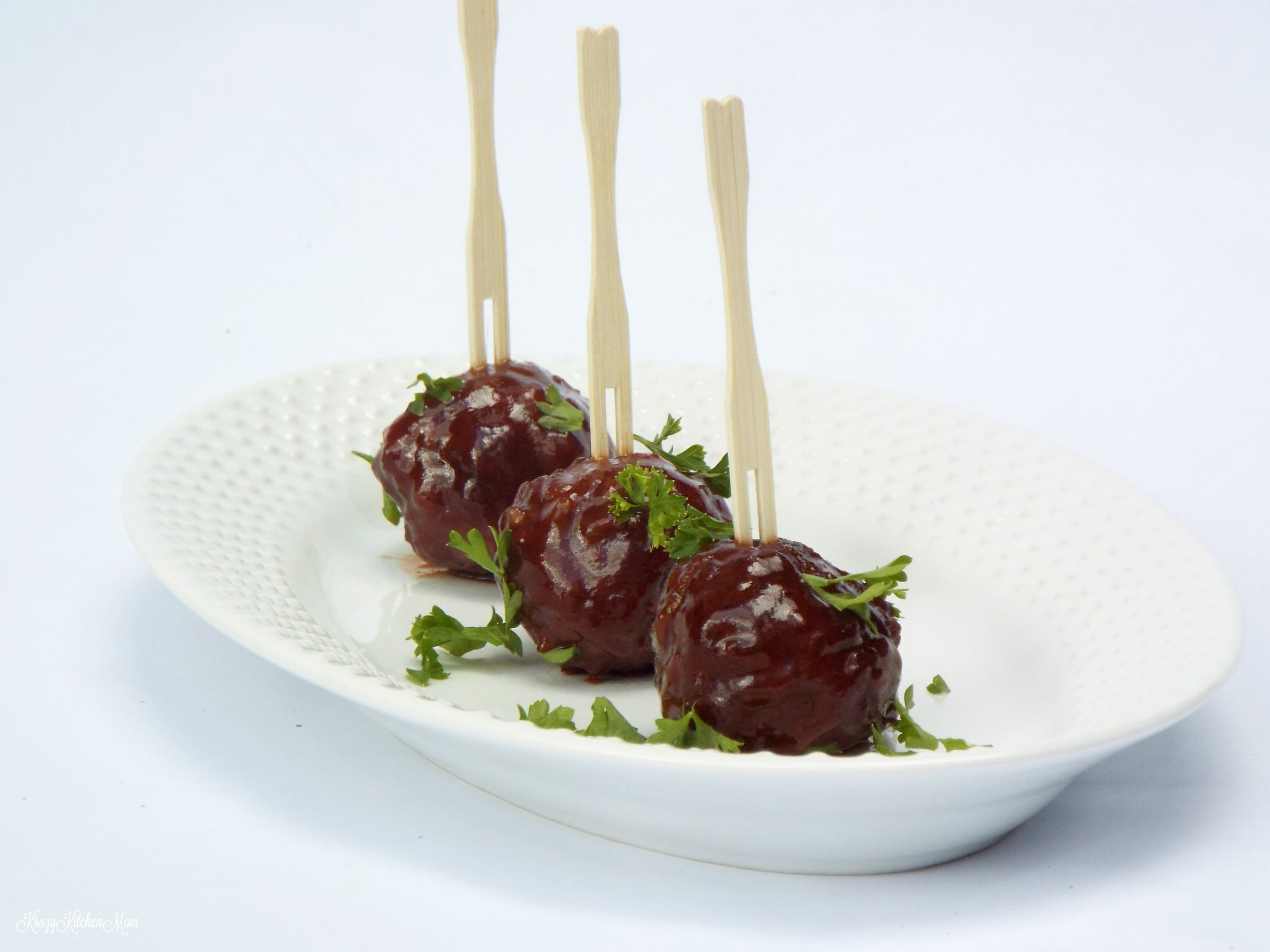 three mini meatballs with skewers on a plate with parsley
