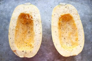 Spaghetti squash cut in half with salt and pepper