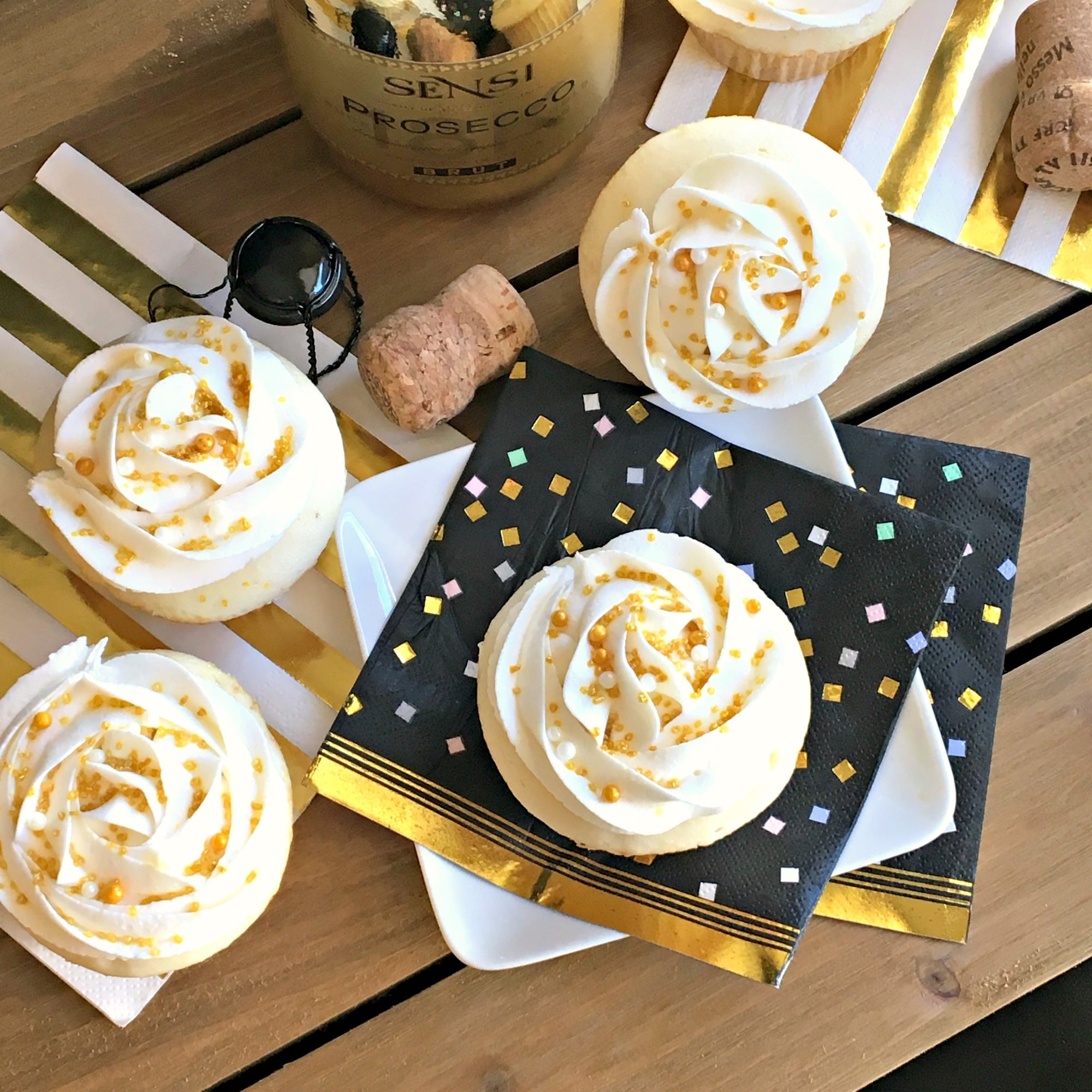 four cupcakes on a board with black and gold napkins