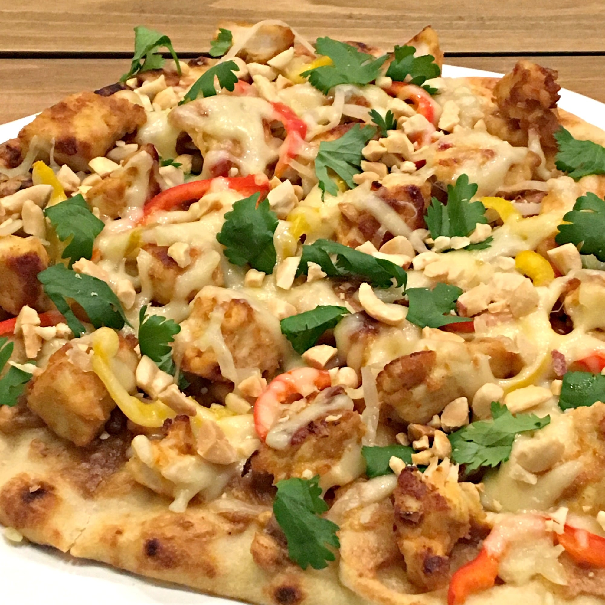 A flatbread topped with chicken, cheese, peanut sauce and cilantro