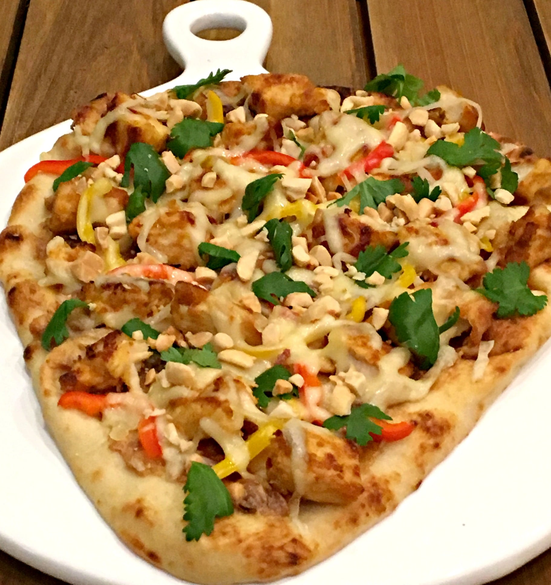 a flatbread topped with chicken, peppers, onions and cilantro