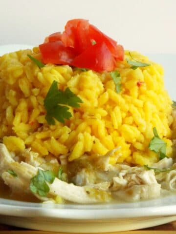 a plate of shredded chicken topped with yellow rice, tomatoes and cilantro