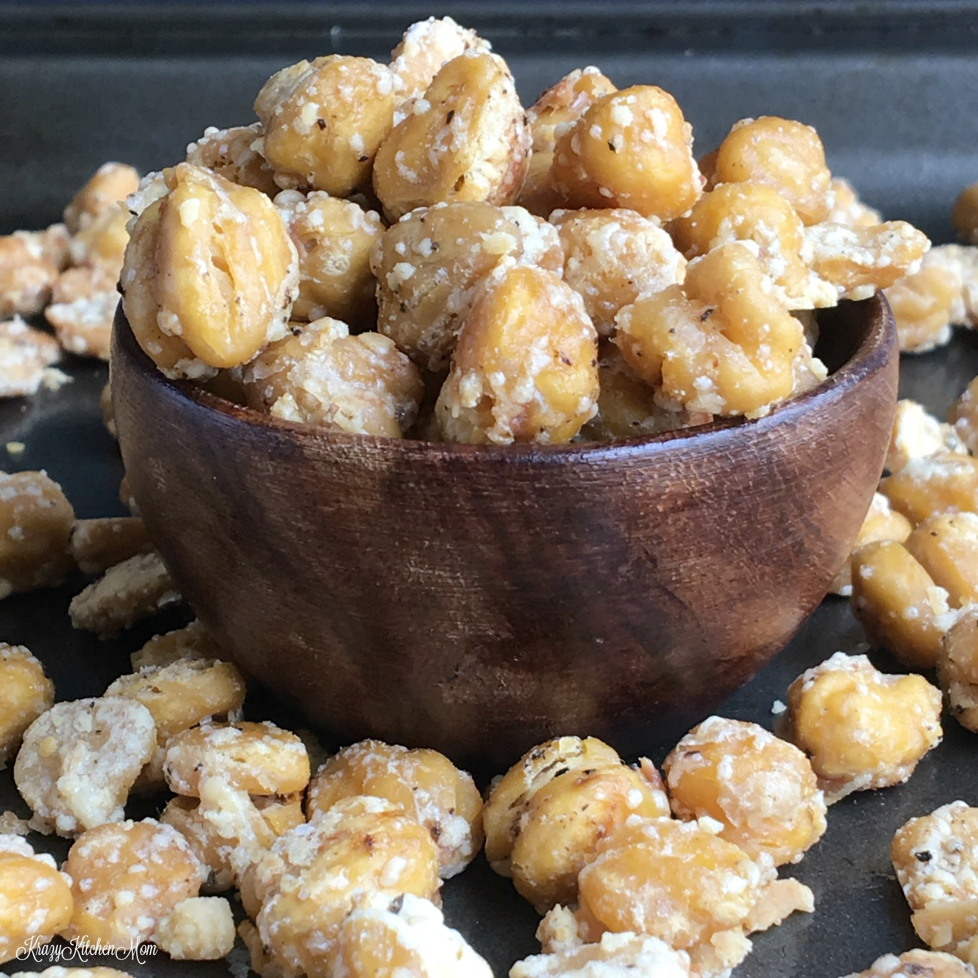 wooden bowl of chickpeas with some spilling out