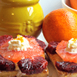 slices of grapefruit and blood oranges with yellow jar in background