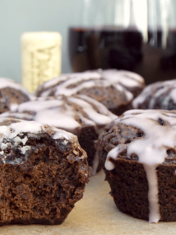 close up of chocolate wine cupcakes with white glaze with a bit out of one cupcake