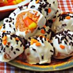 A close up of several cookie balls with sprinkles and a candy corn in center