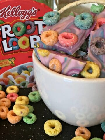 a bowl of candy topped with froot loop cereal with the cereal box in background