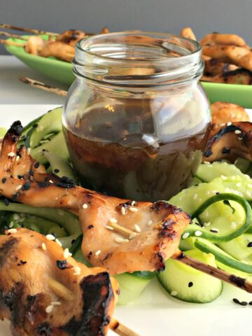 chicken kabobs and cucumber slices with a jar of sauce
