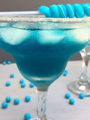 a close up of a blue cocktail with a blue candy stick sitting on top