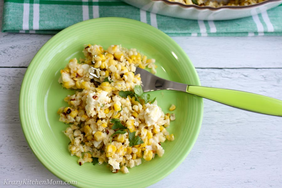 Mexican Street corn on a green plate with fork