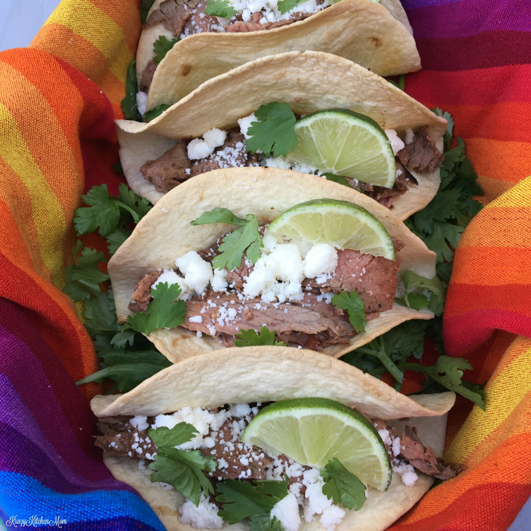 a row of four tacos topped with cheese, lime and cilantro