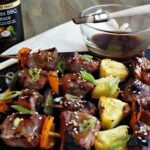 Pork, pepper, pineapple skewers with bowl of sauce and brush in background