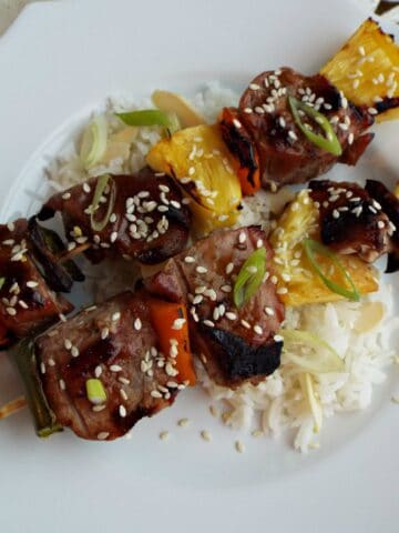 two pork, pepper, pineapple kabobs sitting on white rice