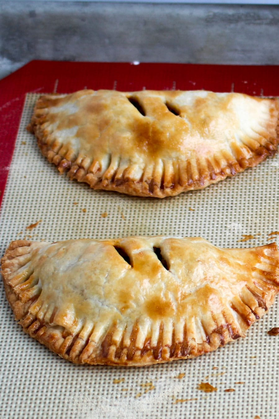 two empanadas on a baking sheet