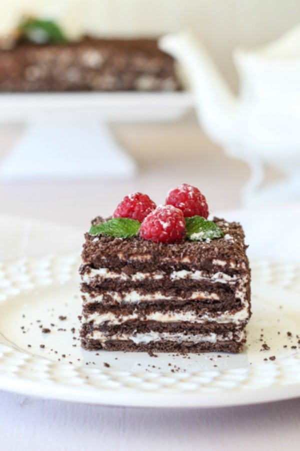 A close up of a piece of cake on a plate with Chocolate and Cheesecake topped with raspberries