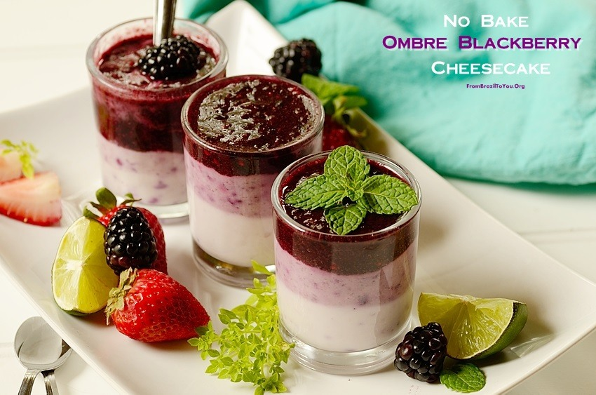 3 dessert dishes filled with layers blackberry cheese cake topped with blackberries and fresh mint