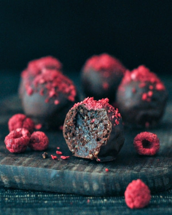 A close up of a dark chocolate truffle candy topped with raspberry dust