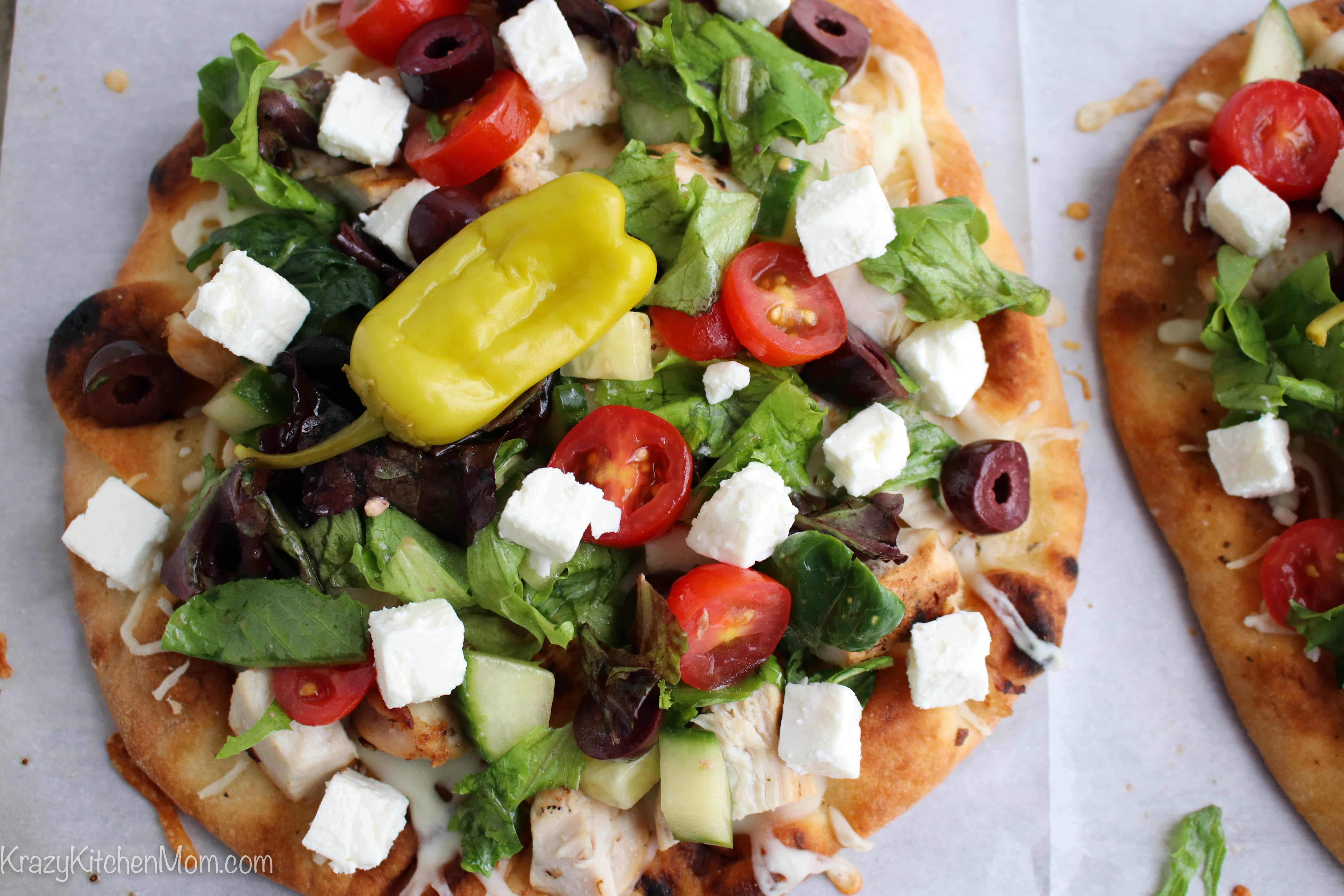 a flatbread topped with Greek salad and a pepper