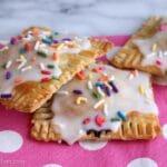 three glazed pop tarts with sprinkles on a pink and white polka dot napkin