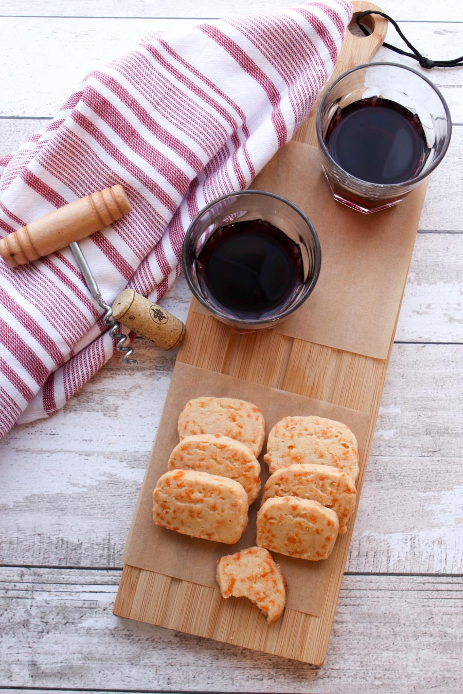 rectangle crackers on a serving board with two glasses of red wine