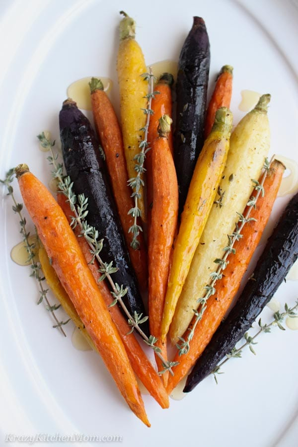Orange, yellow, purple carrots with fresh thyme and honey on a white plate
