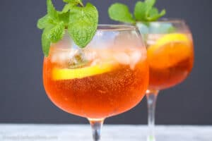 Close up shot of an glass filled with aperol spritz with mint