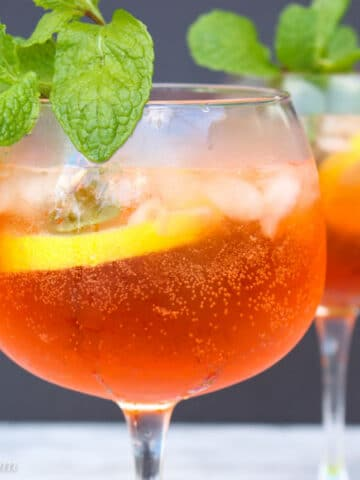Close up shot of an glass filled with aperol spritz garnished with lemon slice and fresh mint