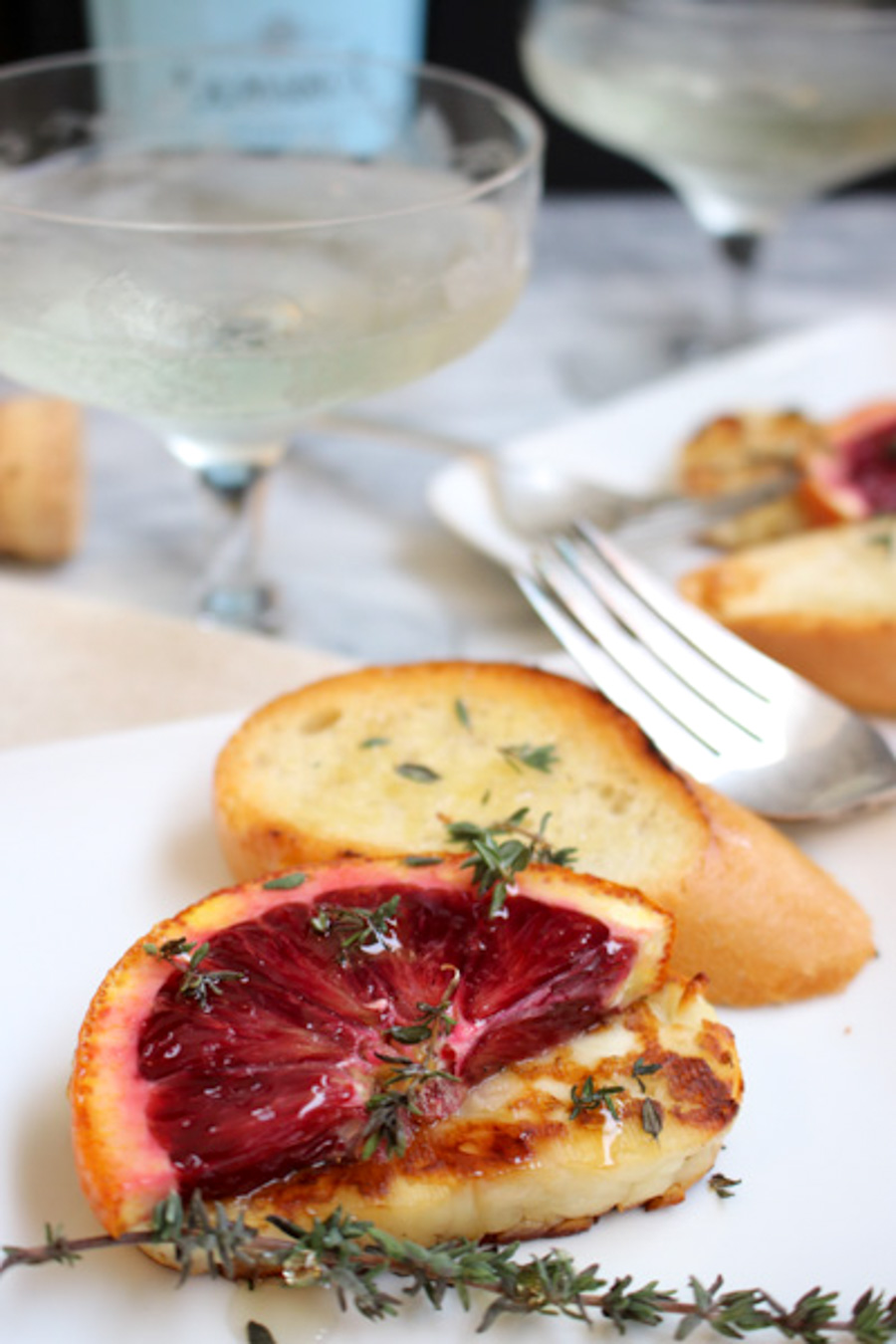 Grilled Halloumi with blood oranges on a plate with bread