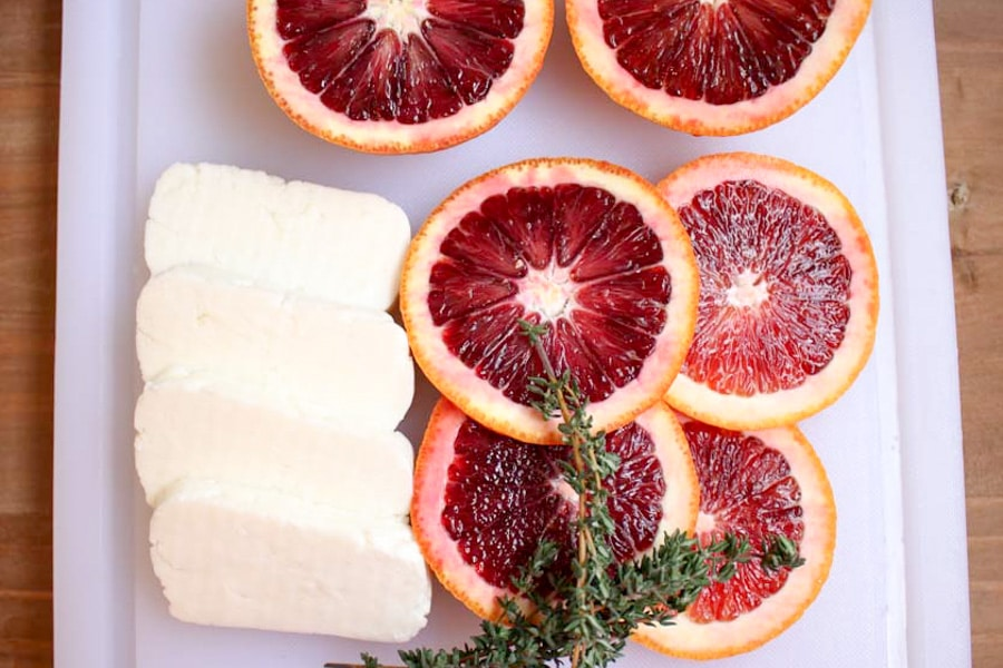 Raw slices of cheese, oranges and herbs ready to cook