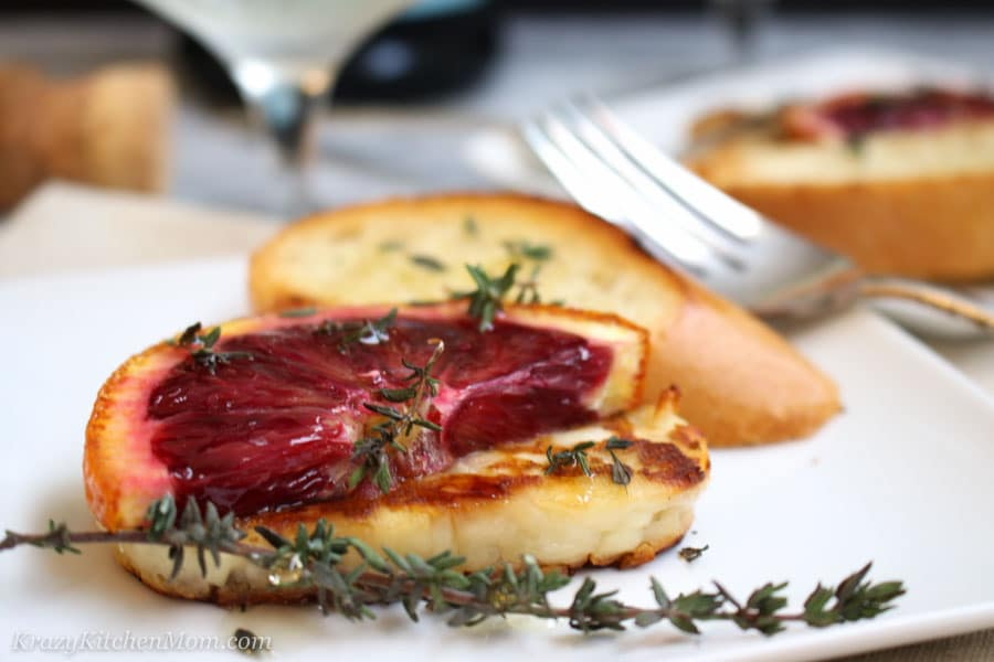 Grilled Halloumi Cheese with Blood Oranges on a plate with a slice of bread