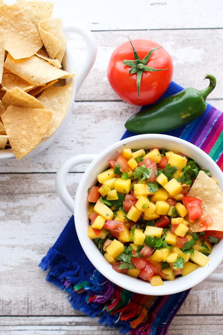 Bowl of mango salsa and a bowl of chips.