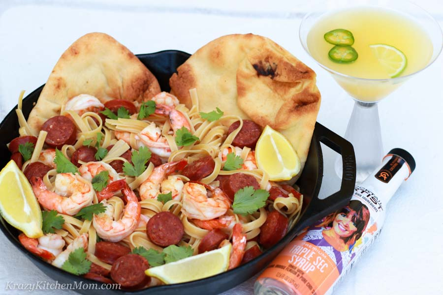 a pan of pasta, shrimp and sausage with a slice of lime and two pitas and a cocktail