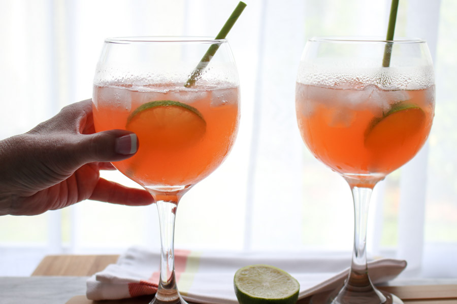 two Paloma Aperol Spritz Cocktails with hand