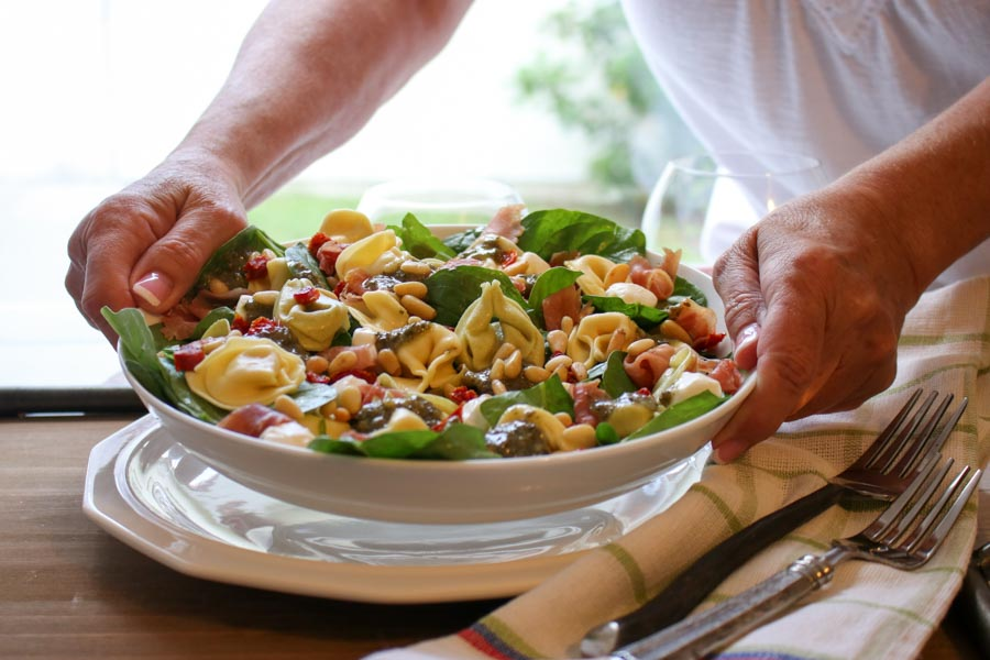 Woman serving Tortellini Spinach Pasta Salad