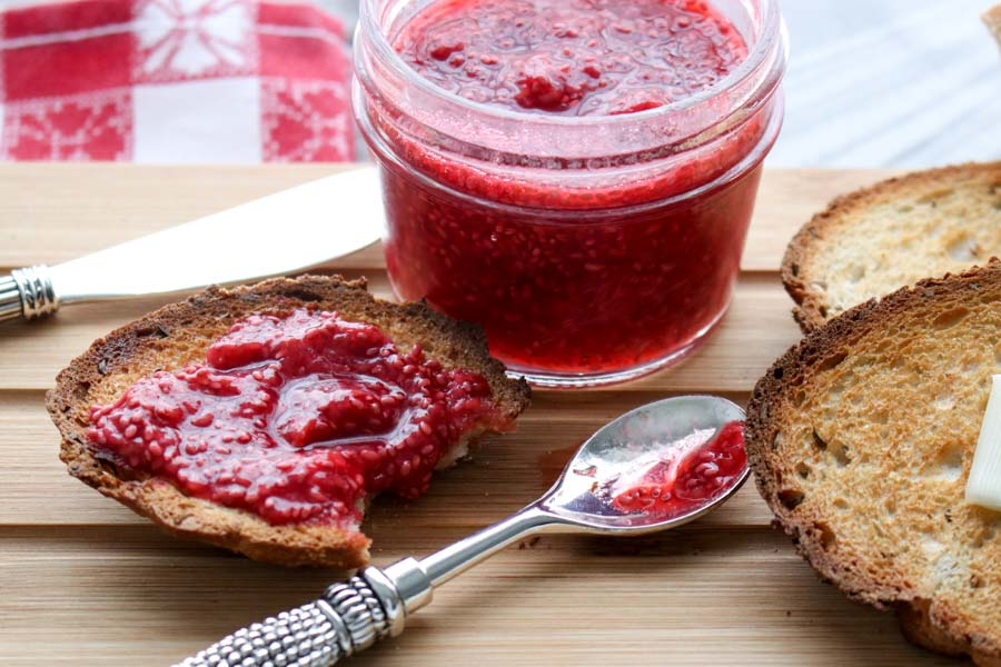 Jar of chia jam with spoon and piece of toast