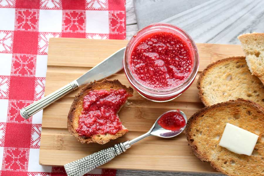 a jar of jam with toast on a cutting board