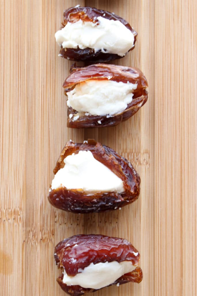 Dates stuffed with cheese on cutting board