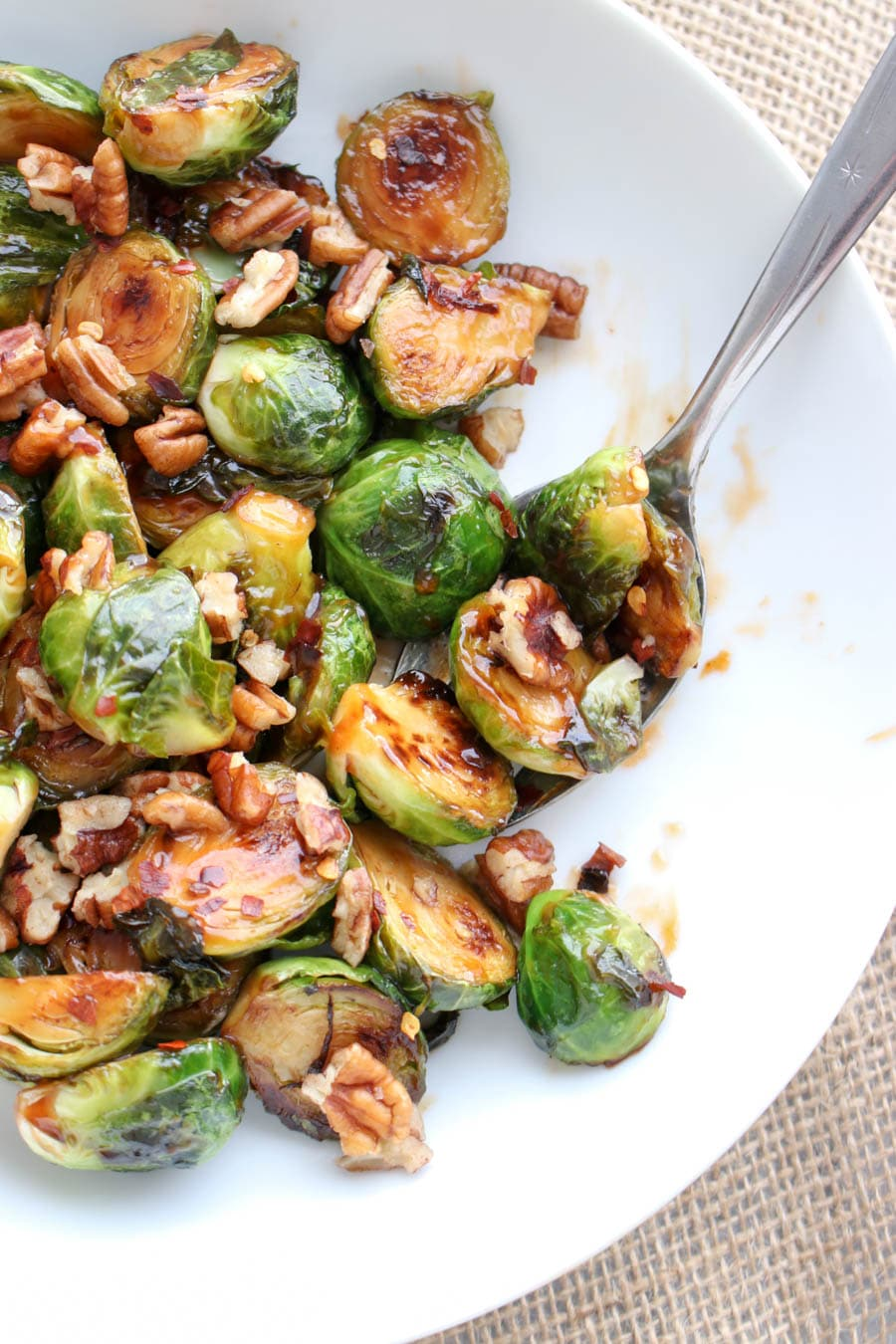 Sweet and Sour Glazed Brussels Sprouts in a serving dish with a spoon