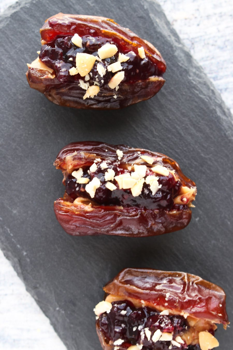 3 Peanut butter and jelly stuffed dates on a tray