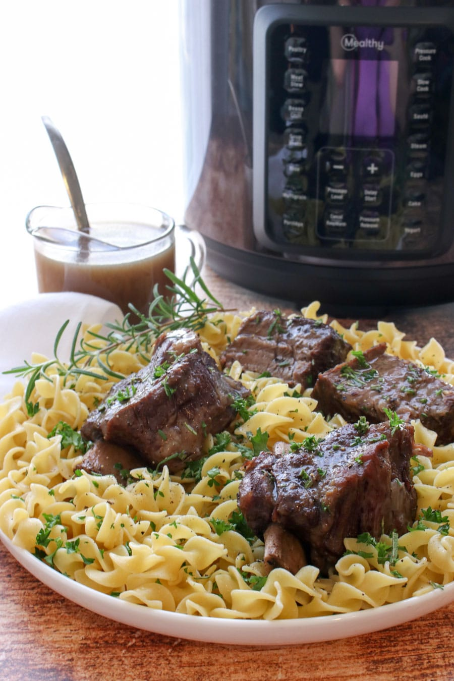 plate of ribs and noodles with pressure cooker in the background