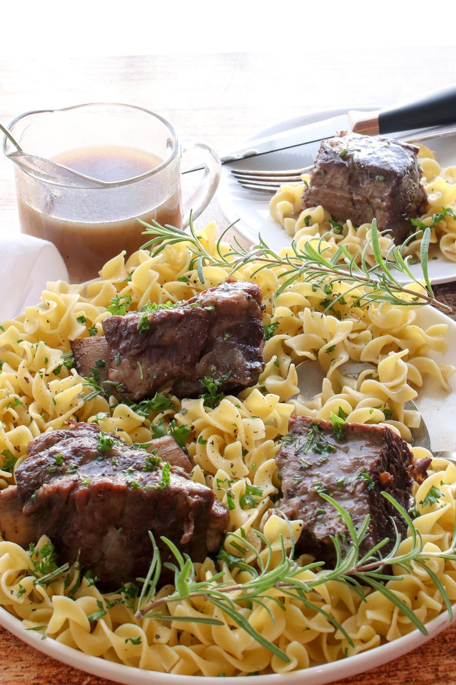 ribs sitting on a plate of noodles