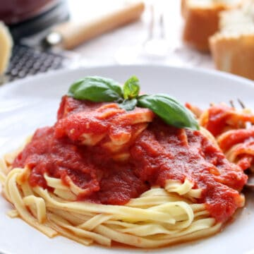 Bowl of sunday sauce on pasta with basil leaf on top